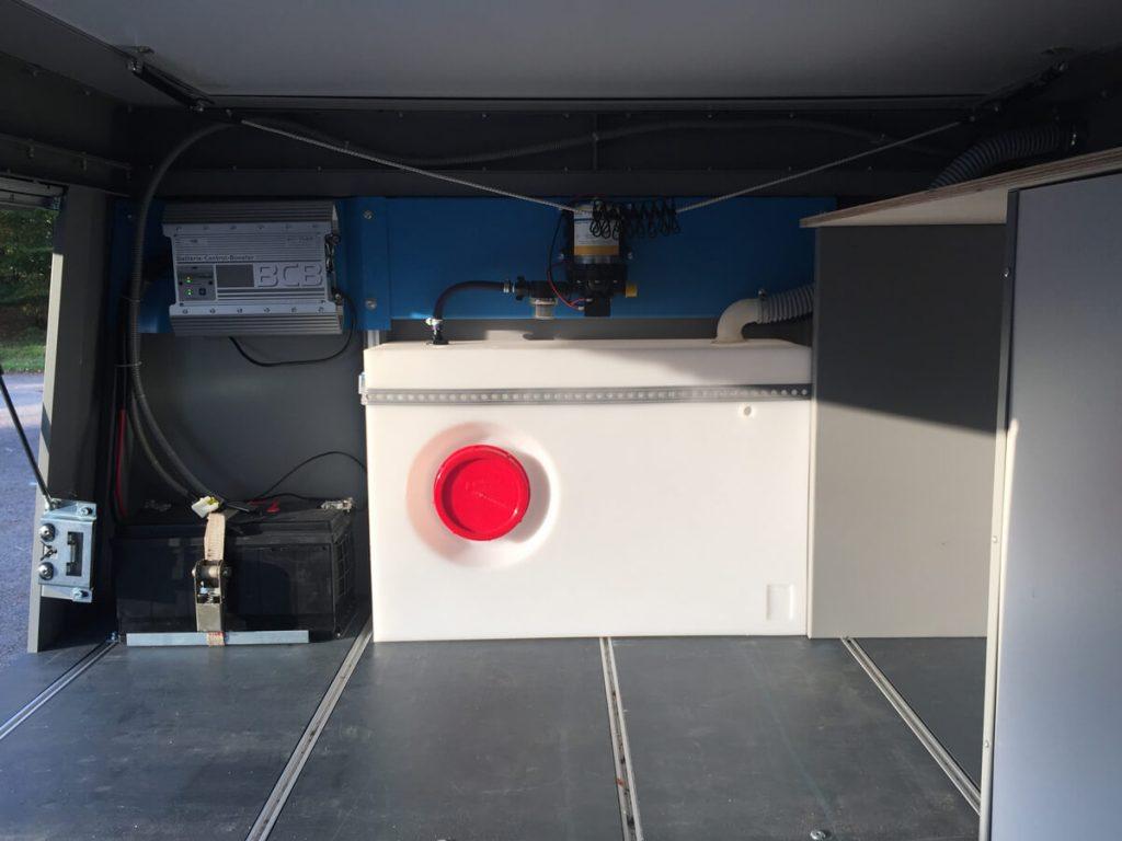 Wassertank mit Pumpe, Bordbatterie und Laderregler an der Stirnwand